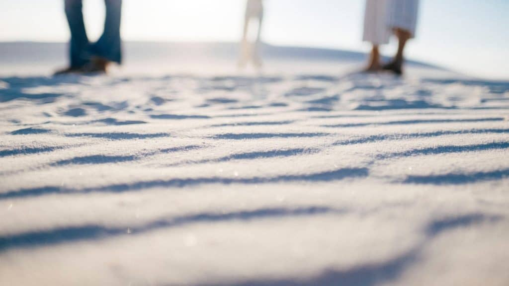 Three people feet down standing on white sands new mexico